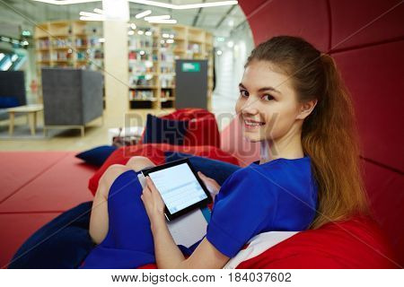 Smiley teenage girl with touchpad spending break in the net