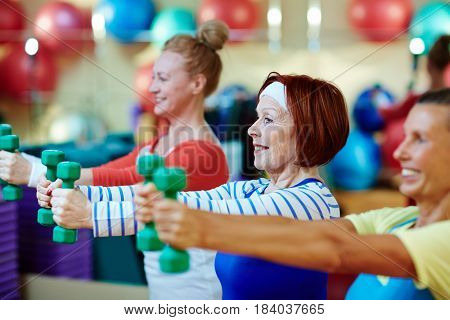 Energetic females stretching arms while exercising with dumbbells