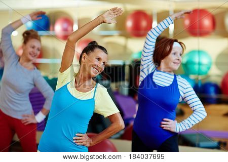 Group of senior females making side-bends in gym