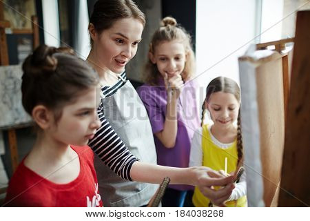 Teacher of painting commenting picture of one of pupils