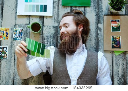 Creative young man looking at green swatches in his hand