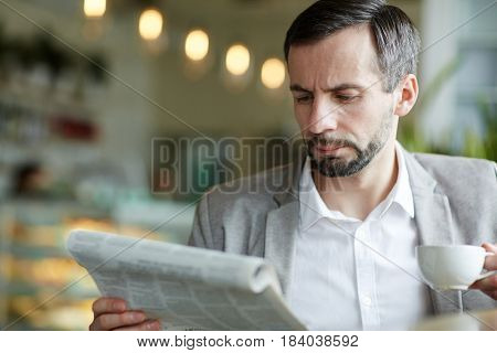 Serious businessman reading newspaper by cup of coffee