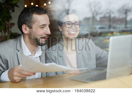 Joyful colleagues reading business data in the internet