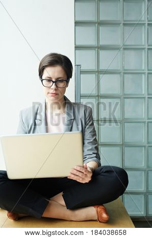Cross-legged businesswoman with laptop working in the net