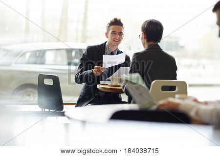 Young agent explaining terms of contract to his client