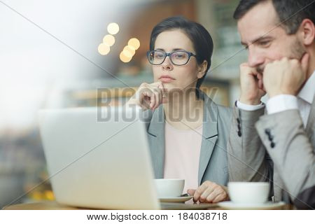 Pensive employees reading online information in laptop