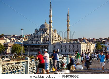 ISTANBUL TURKEY - JULY 9 2014: A fishmen on Galata Bridge in front of Yeni Cami (New Mosque)Istanbul Turkey