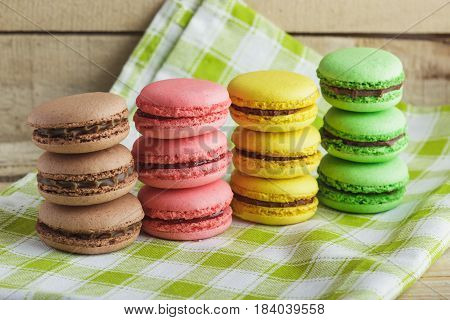 Brown, Yellow, Green And Pink Macarons On The Plaid Napkin