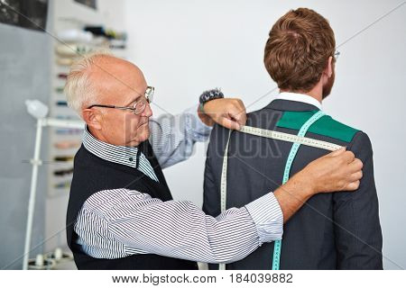 Old fashioned mature tailor taking back measurements from client in small atelier studio to make custom classic suit with jacket