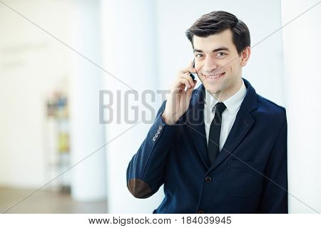 Happy broker speaking on cellphone with client