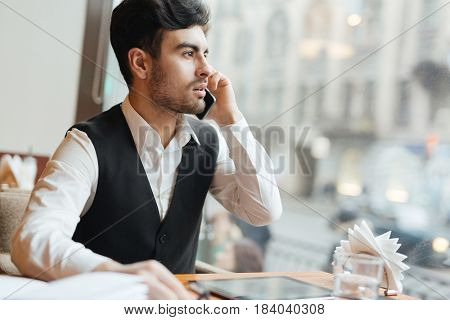 Young trader sitting in cafe and talking to somebody on cellphone