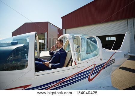 Fast business travel concept: portrait of smiling businessman sitting in cabin of private jet and speaking by phone