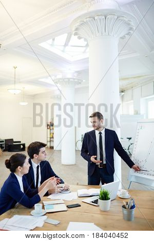Confident young man in suit explaining graph of finances to colleagues