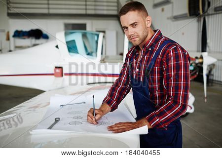 Handsome aircraft engineer reading construction schemes and looking at camera while repairing plane in hangar