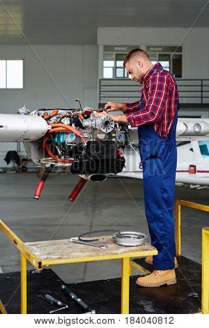Airplane service crew working on preflight maintenance:  young mechanic fixing turbine of jet plane in hangar