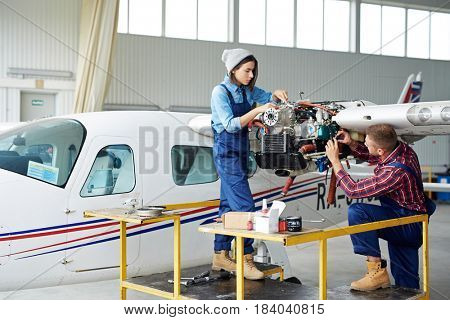 Airplane service crew repairing plane in hangar:  two young mechanics, man and woman, fixing jet plane turbine