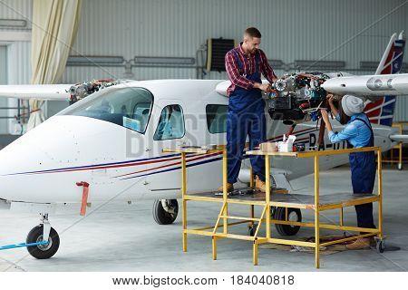 Airplane service crew repairing plane in hangar:  two young mechanics, man and woman, repairing jet plane turbine