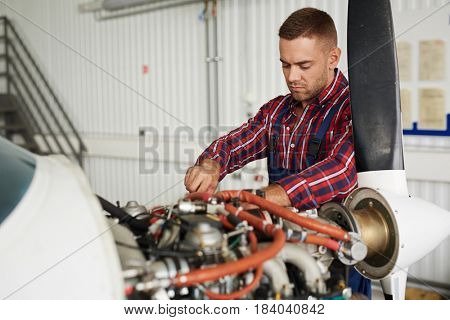 Portrait of handsome young mechanic busy repairing airplane engine in maintenance hangar