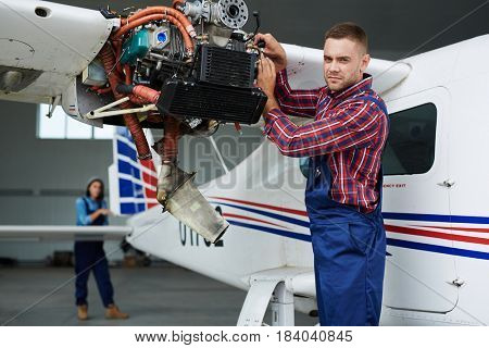 Airplane service team repairing plane in hangar:  modern mechanic fixing disassembled airplane turbine and looking at camera