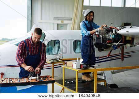 Two modern mechanics, man and woman, repairing jet plane turbine in hangar