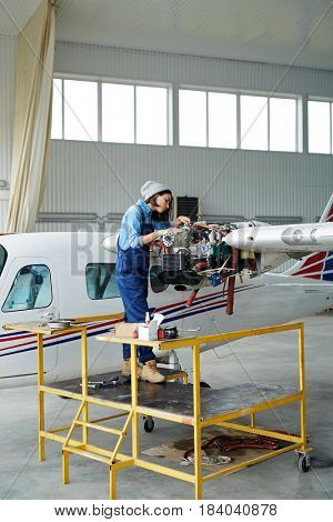 Portrait of modern young woman wearing overalls repairing jet plane turbine in hangar