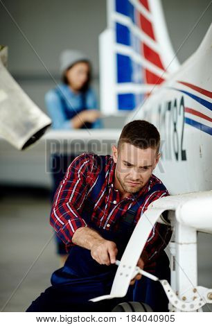 Airplane service crew working on preflight maintenance: strained young mechanic tightening screws in chassis of jet plane