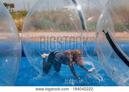 Zorbing Or Globe-riding. Redhead Girl Inside Water Walking Ball