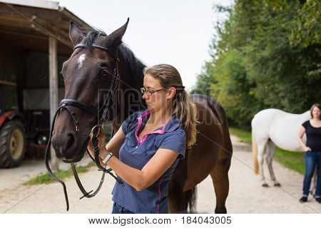 Woman bridling her horse on horse ranch