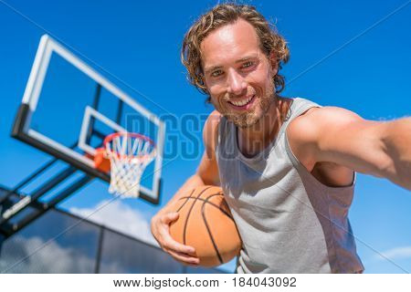 Basketball player man taking fun selfie photo at court net with basket ball.