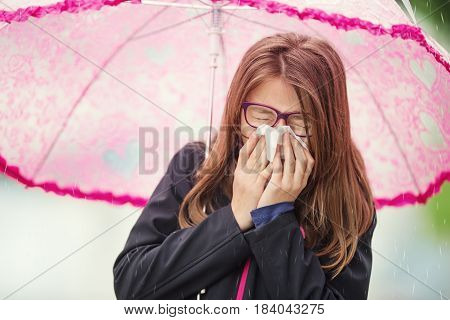Young girl with flu blowing her nose with a tissue paper under spring rain. Pre-teen girl sneezing and wearing warm clothes against cold weather. Depression illness allergy under rain.