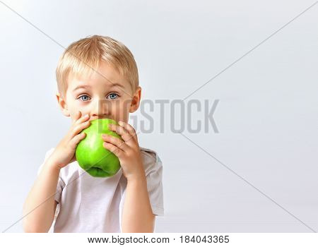 Happy Cheerful Boy Eats The Big Apple, The Child Is The Fruit Green, Soft Focus