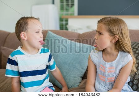 Sister and brother stick out tongues to each other on couch in living room at home