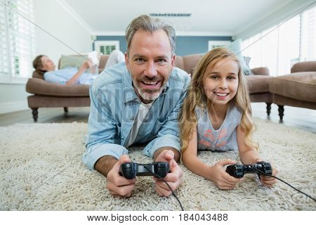 Happy father and daughter playing video game while lying on floor at home