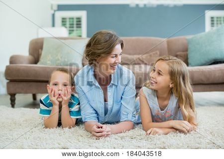 Smiling mother with her son and daughter lying on carpet in living room at home