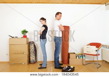 a young couple are separating after living together for a while. the line is drawn on the floor and each has his own stuff, ready to walk out.