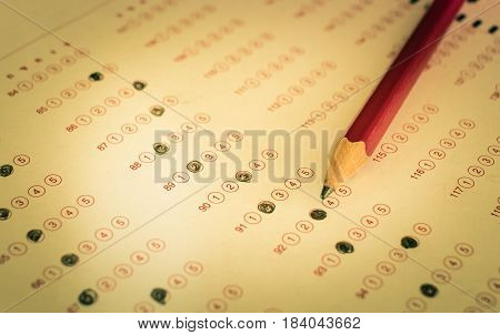 Standardized test exams form with answers bubbled in and color pencil resting on the paper test education concept