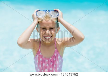 Portrait of smiling girl holding her swimming goggles near swimming pool