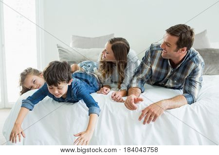 Smiling family playing on bed in bedroom at home