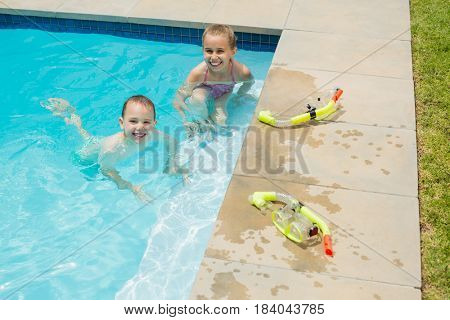 Portrait of smiling boy and girl playing in swimming pool