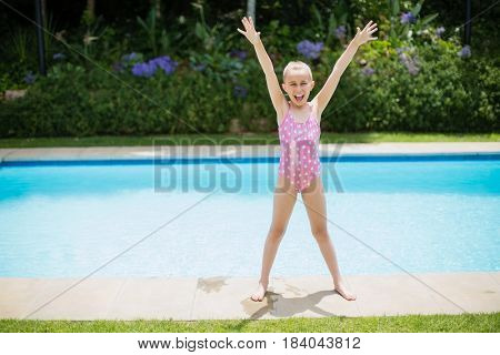 Cheerful girl standing with her hands raised near swimming pool