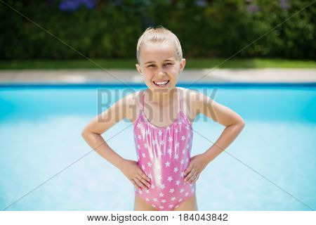 Portrait of smiling girl standing with hands on hip near swimming pool