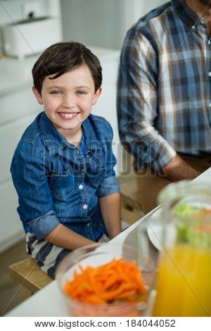 Portrait of smiling boy sitting at dining table in home