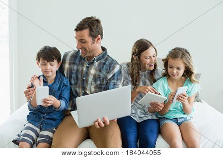 Smiling family using laptop, digital tablet and mobile phone in bedroom at home