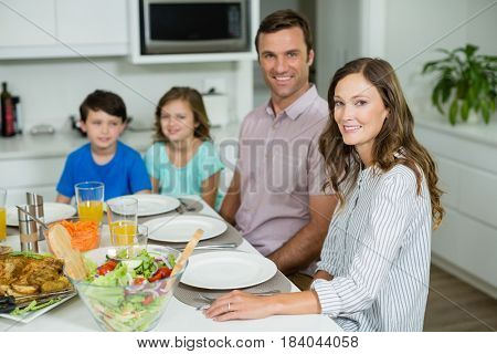 Portrait of smiling family having lunch together on dining table at home