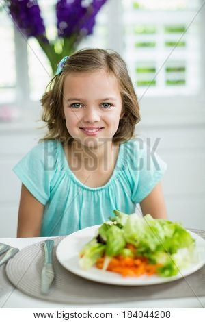 Portrait of smiling girl sitting at dining table at home