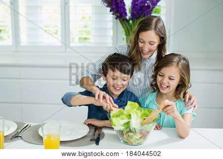 Smiling mother and childrens mixing bowl of salad in kitchen at home