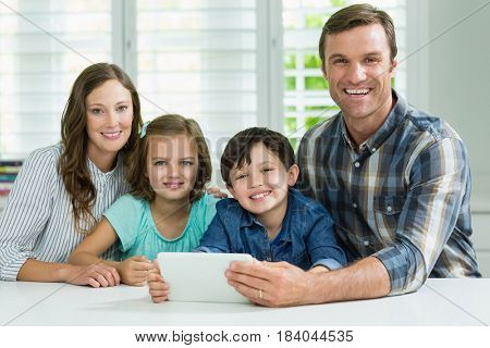 Portrait of smiling family using digital tablet in living room at home