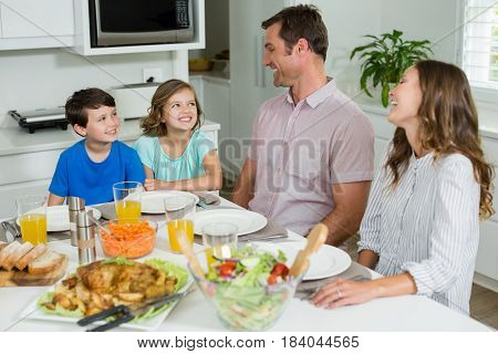 Smiling family interacting with each other while having lunch together at home
