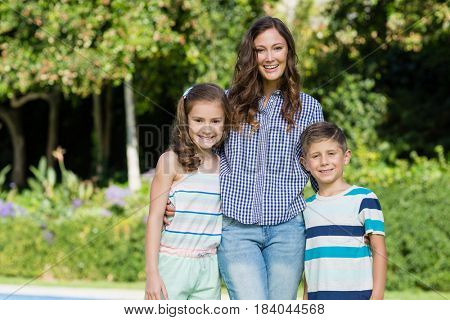 Portrait of smiling mother standing with her son and daughter in garden