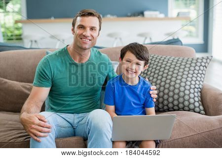 Portrait of smiling father and son sitting on sofa using laptop in living room at home